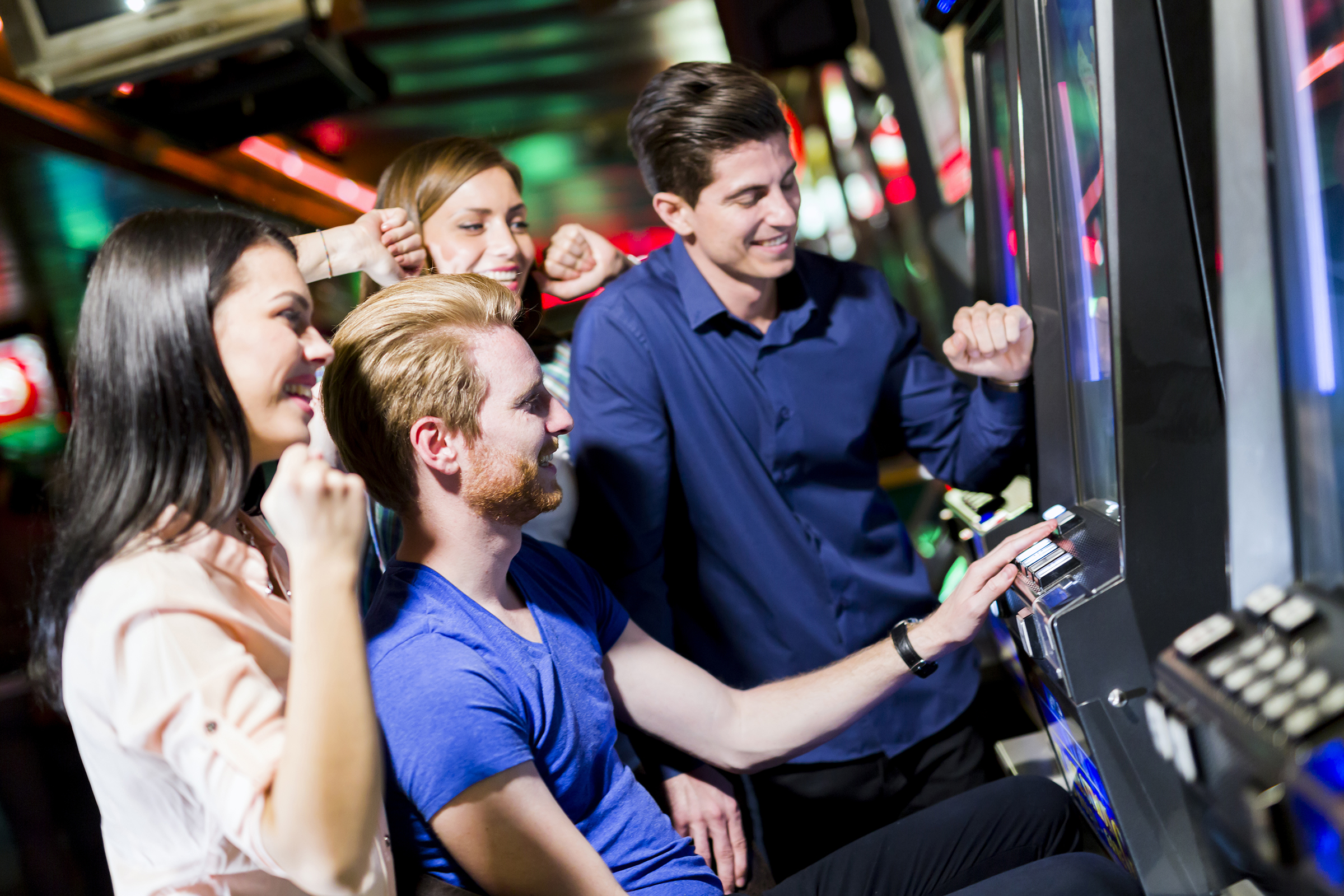 Young group of people gambling in a casino playing slot and various machines
